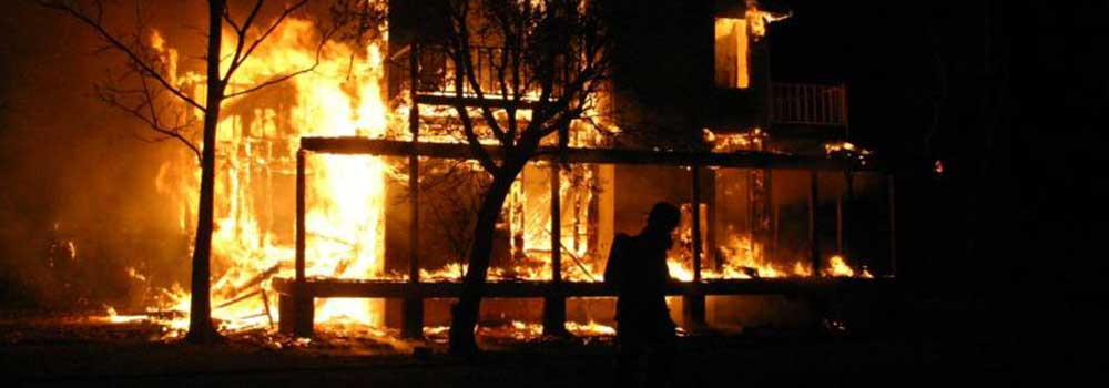 A house burning at night with a fire fighter assessing