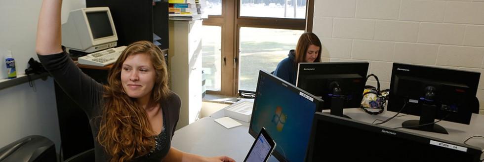 Student raising hand in computer class