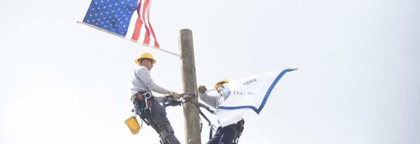 Coastal Powerline students on lineman pole with flags