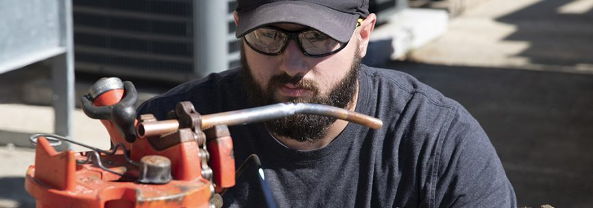 Photo of serious looking student welding pipes together