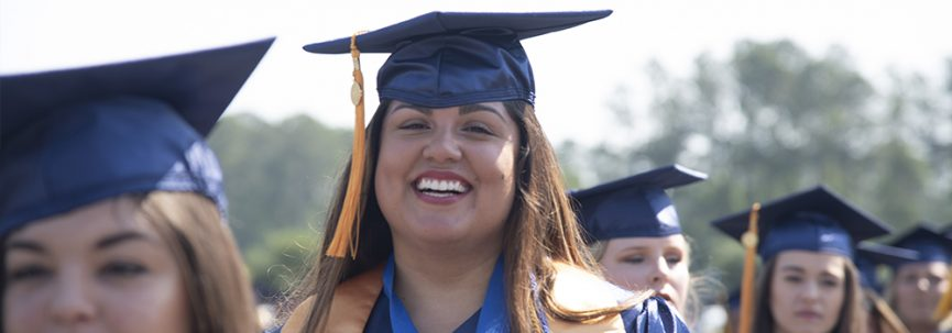 A photo of a student smiling in line at graduation!