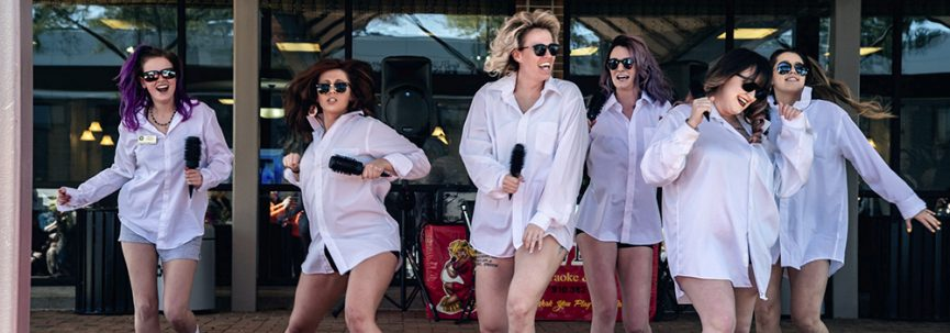 Photo of Six Females In shorts, White long-sleeve shirts, and sunglasses. Dancing and singing into hair brushes.