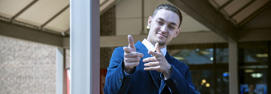 A student wearing business clothing points off screen striking a pose.