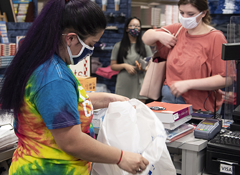 Students wearing masks are checking out at the bookstore.